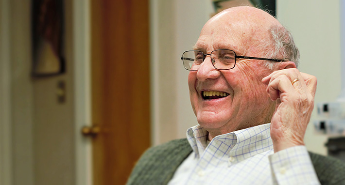 an elderly gentleman grins as he regains his hearing for the first time in years due to properly customized hearing aids